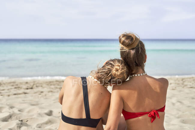 Rear view of two young women on a beach — Stock Photo