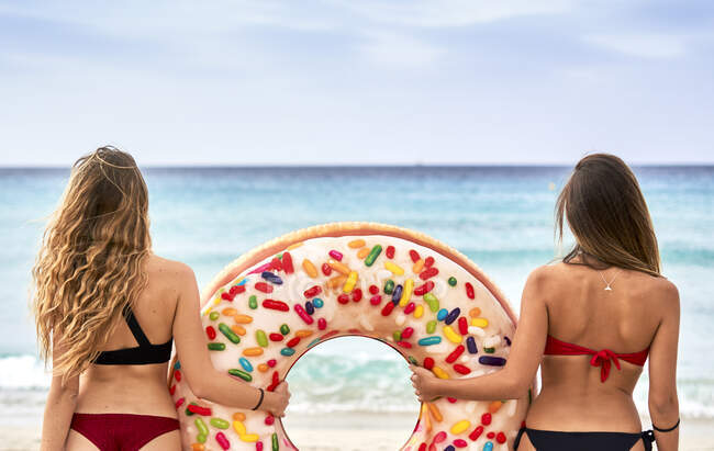 Two young women standing in front of the sea holding a big inflatable ring — Stock Photo