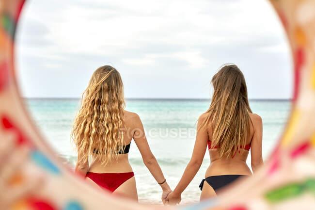 Dos jóvenes mujeres de pie de la mano frente al mar - foto de stock