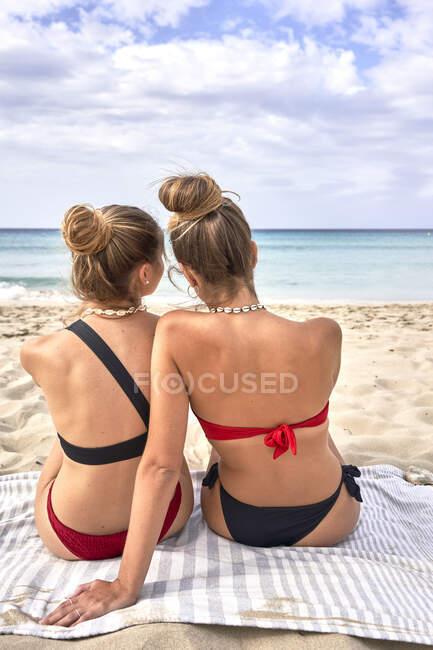 Передній вигляд двох молодих жінок, які сидять на пляжі. — стокове фото