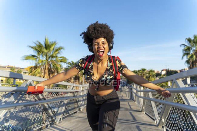 Mujer afroamericana con auriculares y smartphone escuchando música - foto de stock