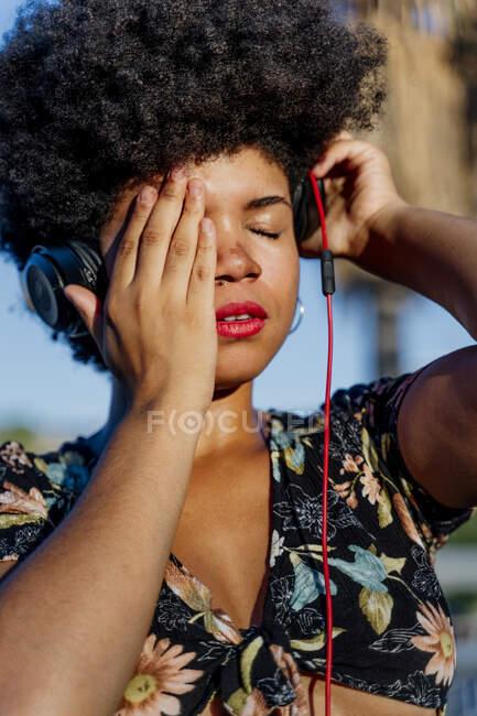 Portait de mujer afroamericana con auriculares y ojos cerrados - foto de stock