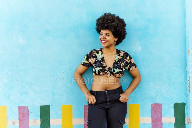Посміхнена афро-американська жінка перед синьою стіною, дивлячись в сторону — стокове фото