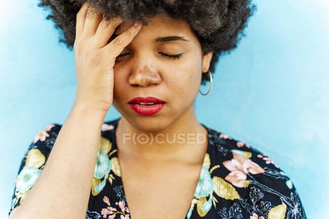 Retrato de mujer afroamericana, mano en la frente, pared azul en el fondo - foto de stock
