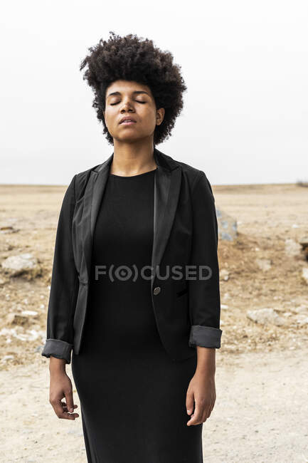 Portrait of young woman dressed in black standing in bleak landscape — Stock Photo