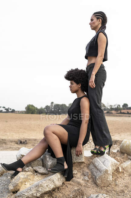 Two womendressed in black on heap of rubble looking at distance — Stock Photo