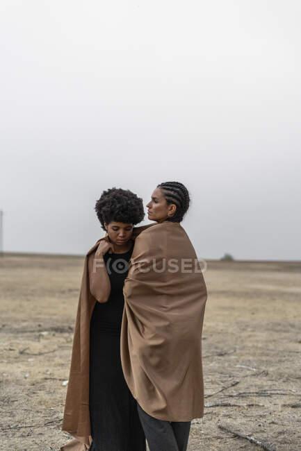 Deux femmes debout dans un paysage sombre partage couverture — Photo de stock