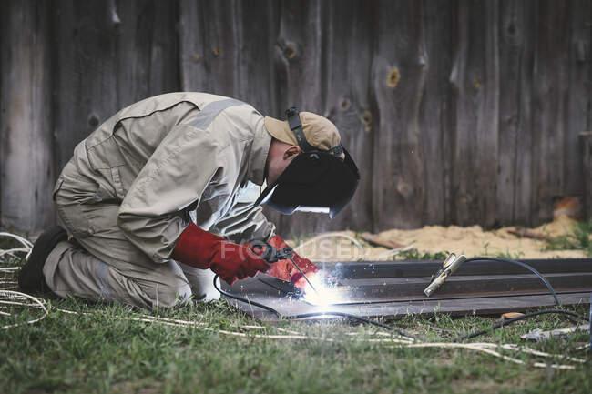 Man welding metal in his backyard — Stock Photo
