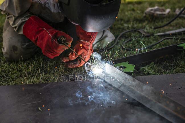 Homem soldando metal em seu quintal — Fotografia de Stock
