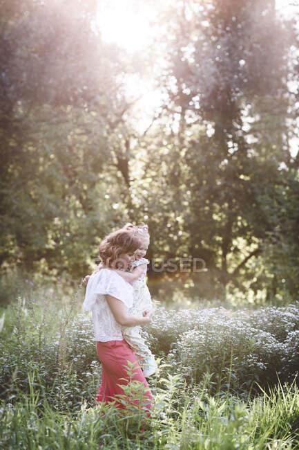Мама носила доньку на квітковій луці. — стокове фото