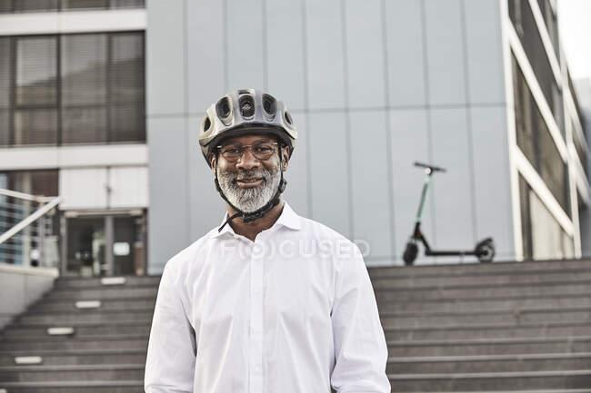 Portrait d'homme d'affaires mature souriant avec E-Scooter portant un casque de cyclisme — Photo de stock