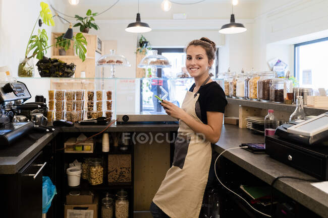 Портрет усмішки молодої жінки з мобільним телефоном у кафе. — стокове фото