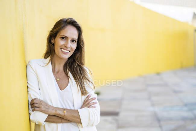 Retrato de una mujer sonriente apoyada en una pared amarilla - foto de stock