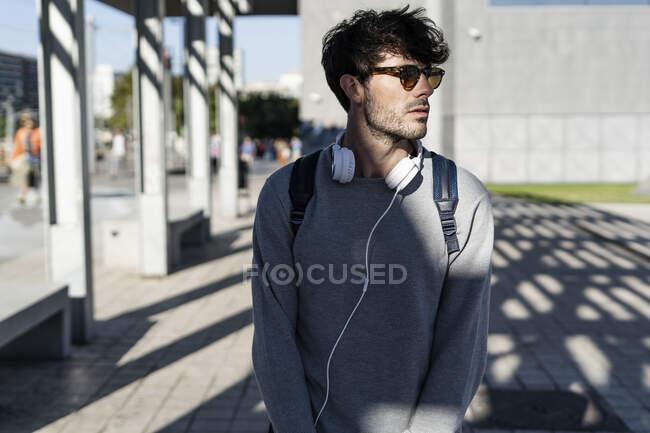 Людина з сонцезахисними окулярами і навушниками, що дивляться навколо в місті — стокове фото