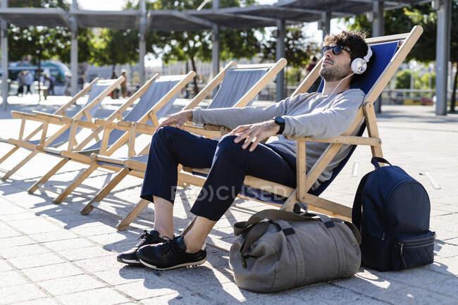 Homem relaxante em cadeira de praia na praça urbana ouvindo música — Fotografia de Stock
