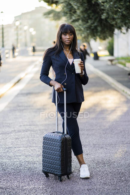 Portrait of a businesswoman with suitcase and coffe to go outdoors — Stock Photo