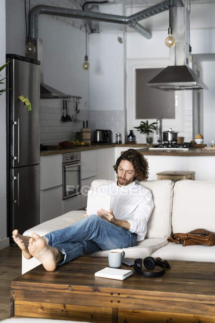 Relaxed man sitting on couch at home using tablet — Stock Photo