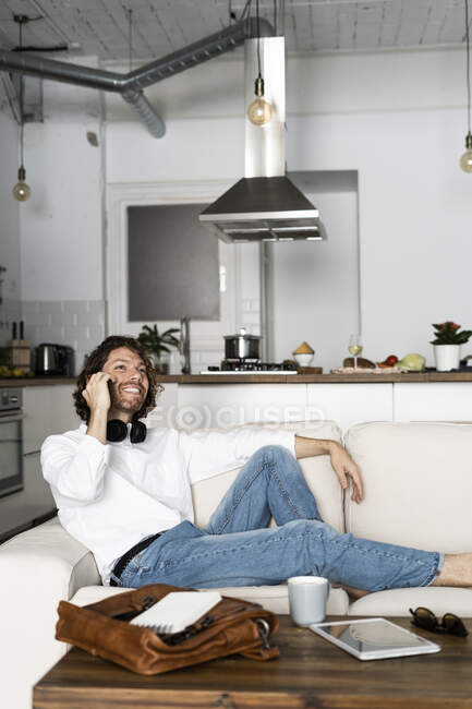 Relaxed man sitting on couch at home talking on the phone — Stock Photo