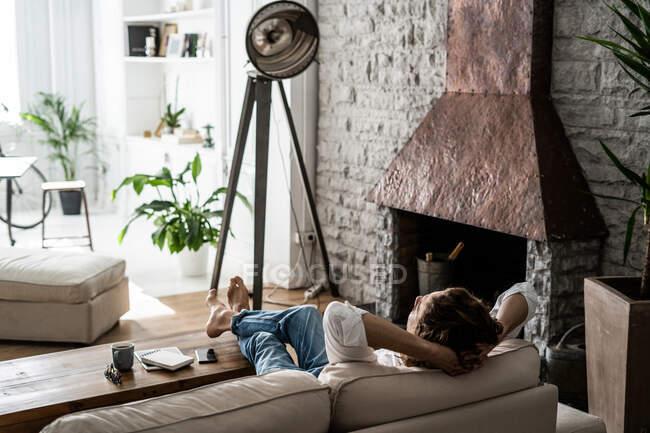 Розслаблений чоловік повертається додому на диван. — стокове фото