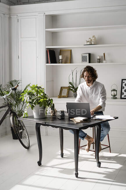 Man sitting at table at home using laptop — Stock Photo