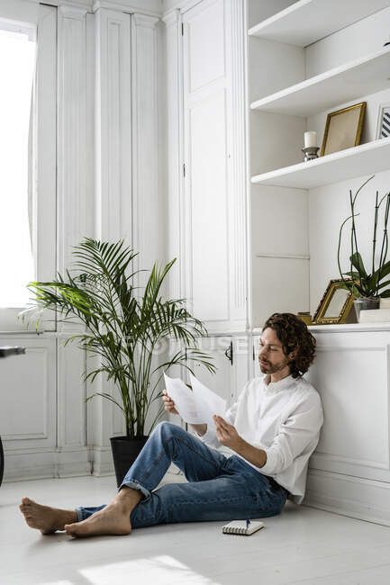 Man sitting on the floor at home reviewing papers — Stock Photo