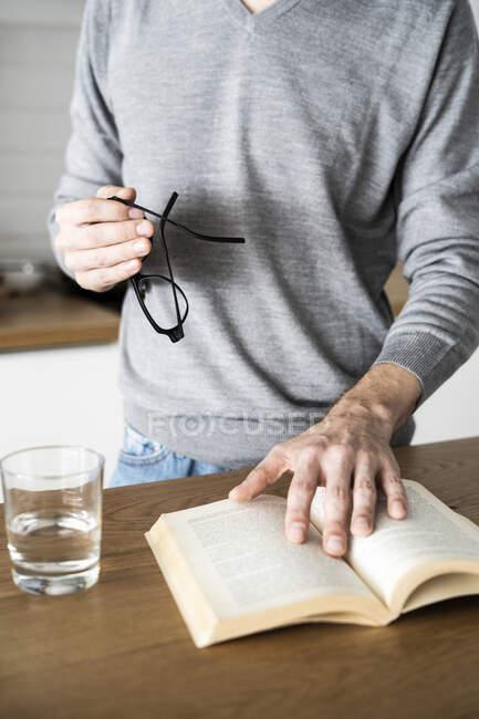 Primer plano del libro de lectura del hombre en la cocina en casa - foto de stock