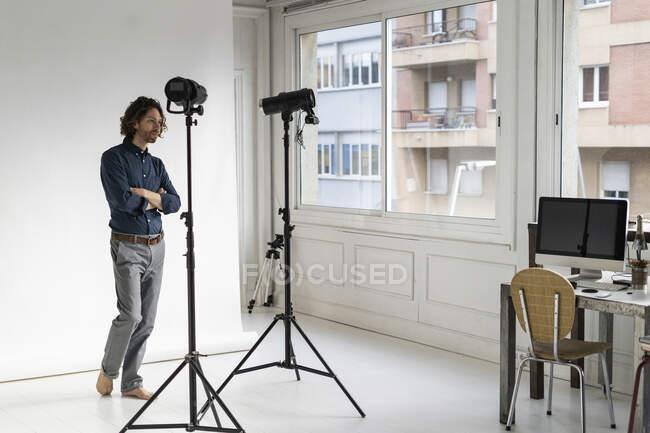 Fotógrafo de pie en su estudio - foto de stock