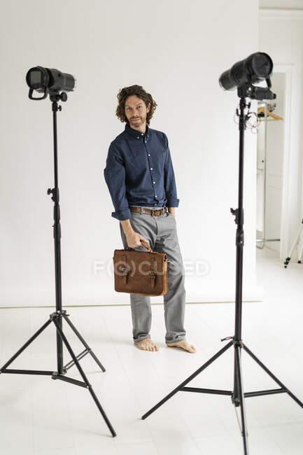 Retrato de un fotógrafo sosteniendo una bolsa en su estudio - foto de stock