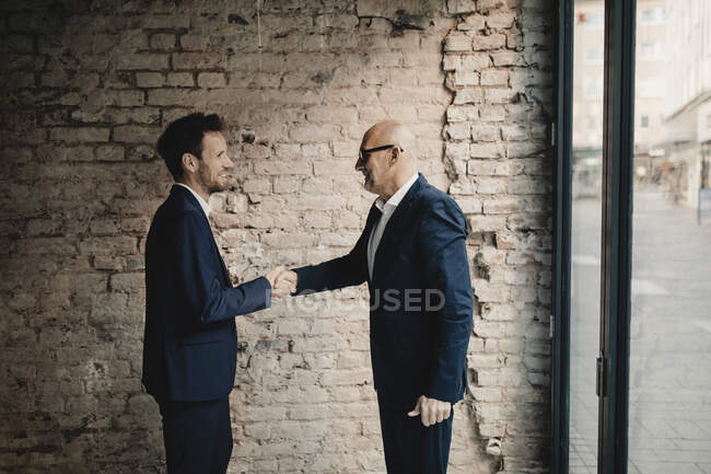 Senior and mid-adult businessmen shaking hands — Stock Photo