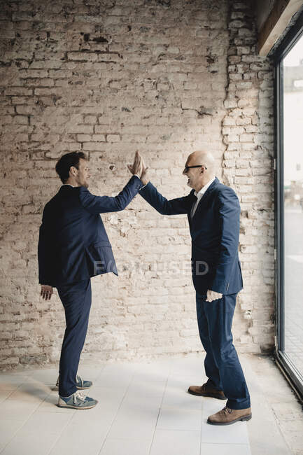 Senior and mid-adult businessmen high fiving — Stock Photo