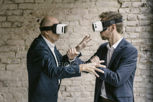 Senior and mid-adult businessmen wearing VR glasses fighting — Stock Photo