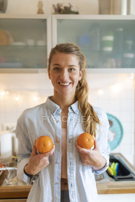 Portrait of happy young woman holding oranges at home — Stock Photo