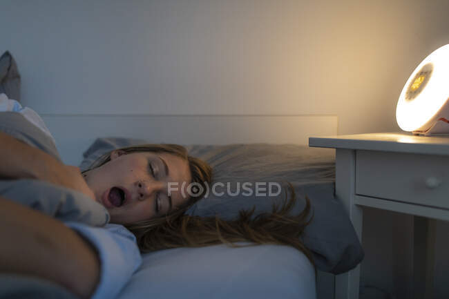 Young woman lying in bed at home at night yawning — Stock Photo