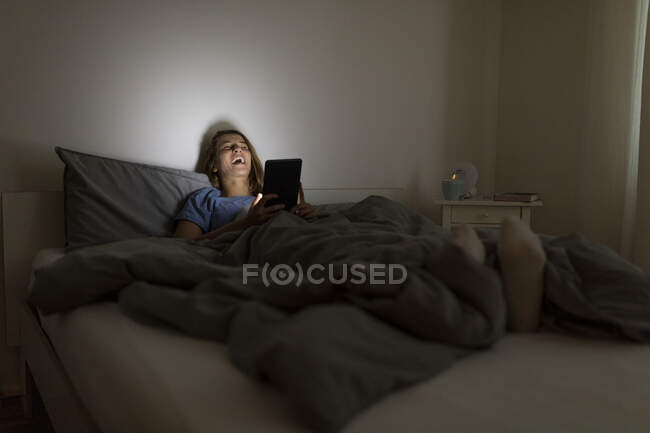 Laughing young woman lying in bed at home at night using tablet — Stock Photo