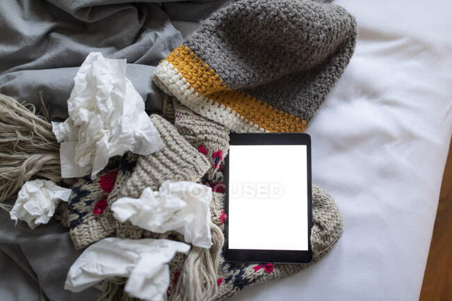Tissues, tablet and warm clothes lying on bed — Stock Photo