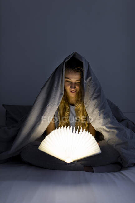 Young woman reading illuminated book in bed at home — Stock Photo