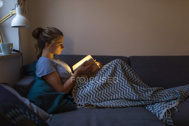 Young woman reading illuminated book on couch at home — Stock Photo