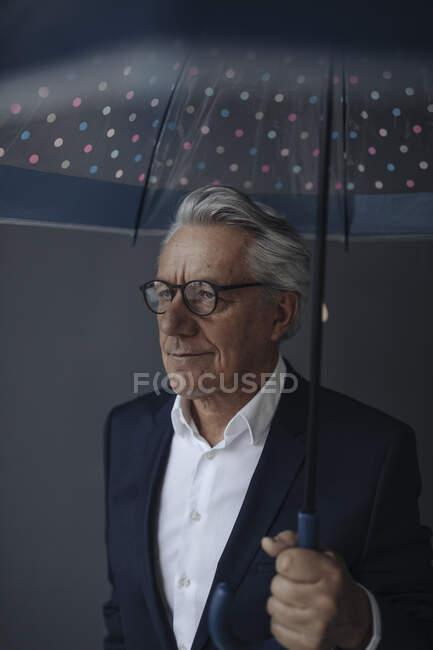 Портрет старшего бизнесмена с зонтиком — стоковое фото