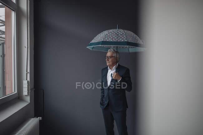 Старший бізнесмен тримає парасольку. — стокове фото