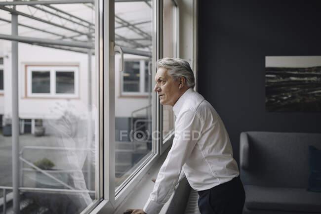 Старший бизнесмен смотрит в окно — стоковое фото