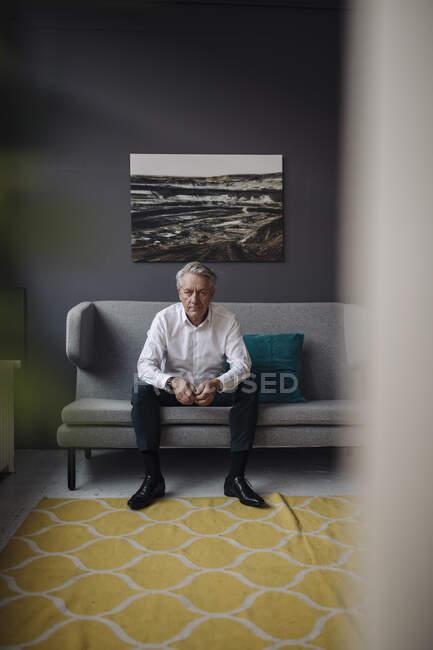 Портрет старшего бизнесмена, сидящего на диване — стоковое фото