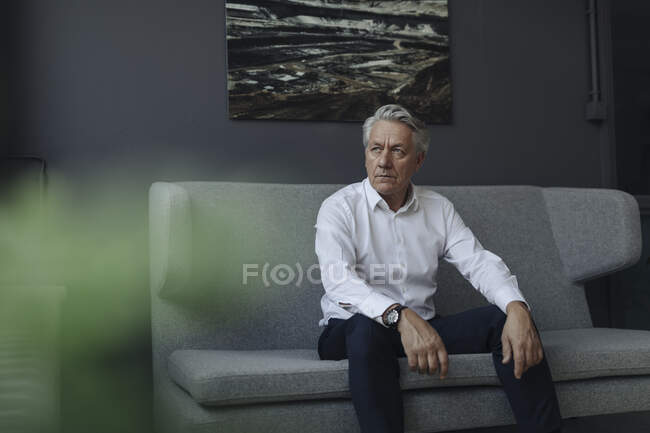 Senior businessman sitting on a couch — Stock Photo