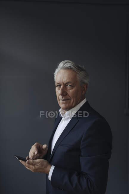 Портрет старшего бизнесмена с мобильным телефоном — стоковое фото