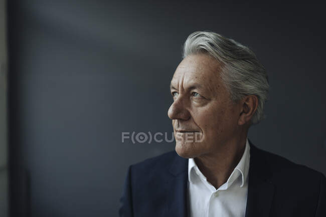 Портрет старшего бизнесмена, смотрящего в сторону — стоковое фото