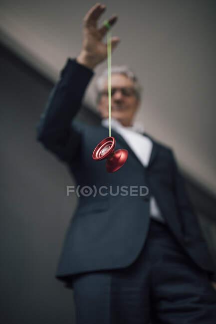 Старший бизнесмен играет с йойо — стоковое фото