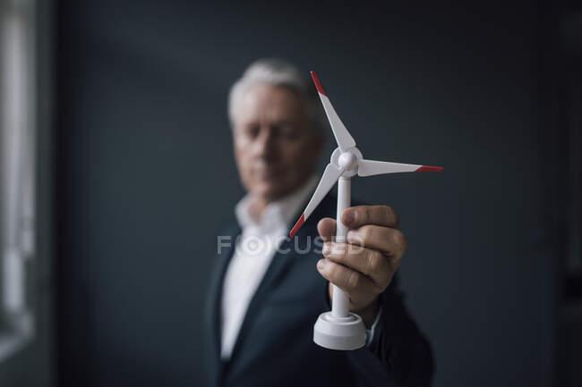 Старший бизнесмен держит модель ветряных турбин — стоковое фото