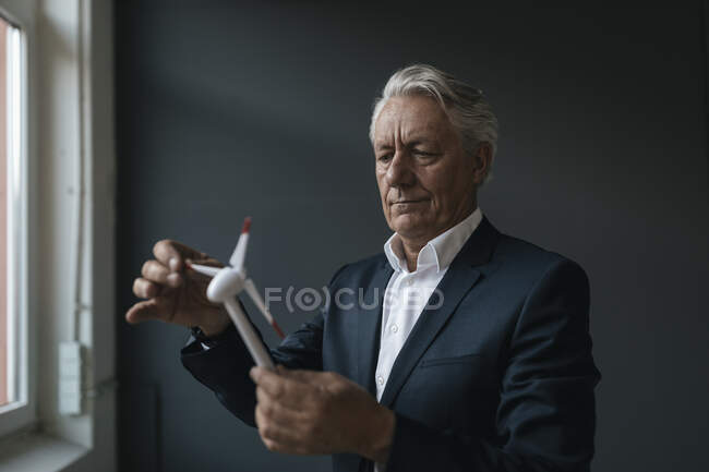 Senior businessman holding wind turbine model — Stock Photo