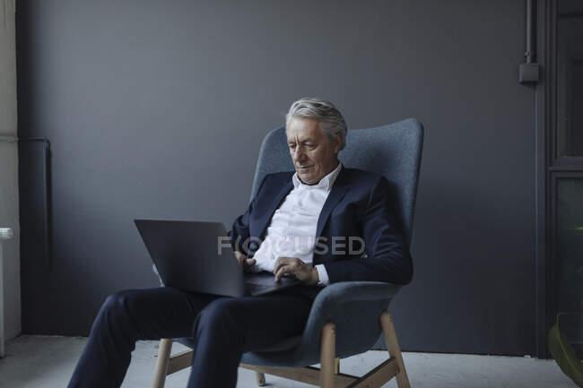 Старший бизнесмен сидит в кресле с ноутбуком — стоковое фото