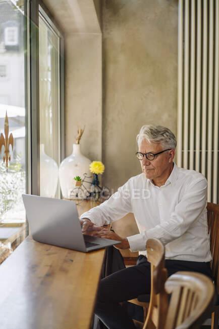 Старший бизнесмен использует ноутбук в кафе — стоковое фото