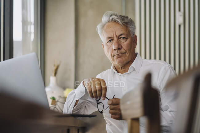 Portrait of senior businessman with laptop in a cafe — Stock Photo